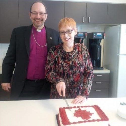 Gina cutting the cake with Bishop Poole